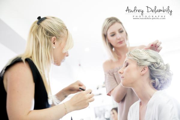Une future mariée en train de se faire maquiller et coiffer lors des préparatifs de mariage
